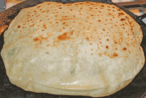 Roti flipped to cook other side, continuing to rise on tava/pan.Rotis gently pressed with a spatula to increase rising of roti